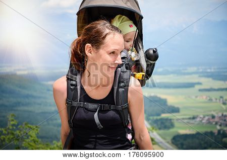 Mother With Baby In Backpack Carrier Is Hiking In Mountains.