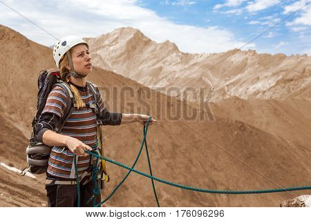 Old Style image of Female Climber working with Rope equipped in Safety climbing Gear protection Helmet and Harness