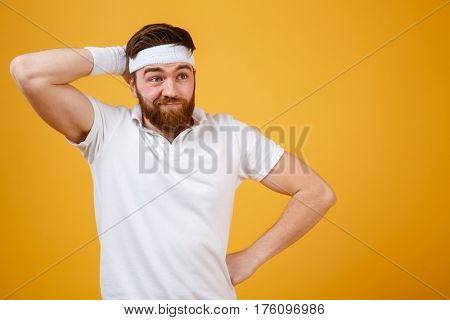 Thoughtful bearded sportsman which scratching his head and looking away. Isolated orange background