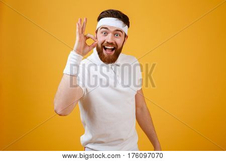 Happy sportsman with open mouth which showing ok sign and looking at camera. Isolated orange background.