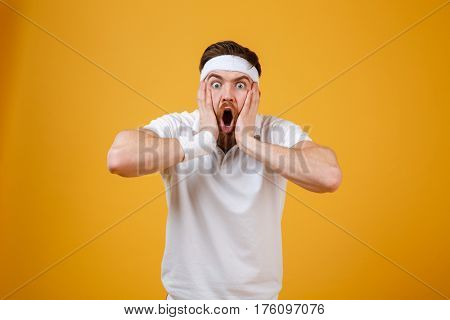 Shocked sportsman which holding his cheeks while looking at camera. Isolated orange background