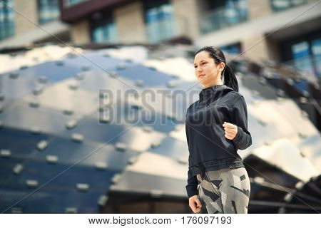 Active sporty dressed girl holding mobile phone and walk