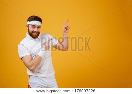 Happy bearded sportsman which pointing up and looking at camera. Isolated orange background