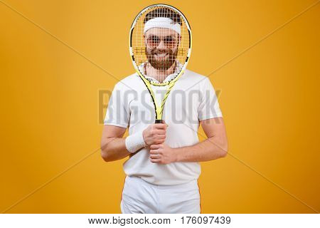 Smiling sportsman in sunglasses which looking through the tennis racquet. Isolated orange background