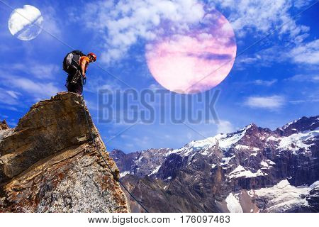 Brave Mountain Climber in bright shirt and helmet staying on sharp rocky peak and looking down Alien planetary sky on background