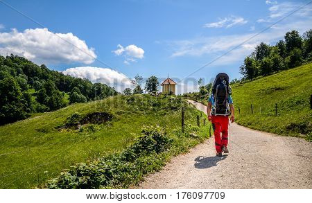 Father with baby in backpack carrier is hiking in mountains. Tourist is carrying a child on his back in the nature of Slovenia.