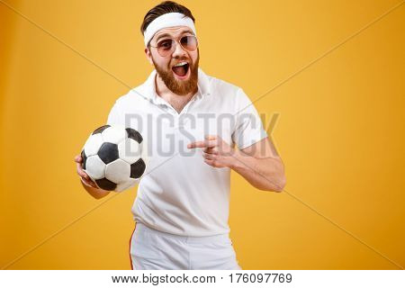Happy sportsman in sunglasses and with open mouth which holding soccer ball and pointing at him. Isolated orange background