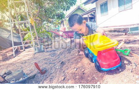 Thai Baby Boy Palying On  Pile Of Sand With Toy
