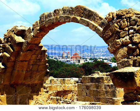 The Ayioi Anargyroi Churchin Paphos, Cyprus, seen through the ruins of the Saranda Kolones Fort inside the Archeological Park.