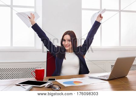 Sucessful project. Happy business woman sitting at table in office and keeping arms with documents outstretched , enjoying new achievement. Female manager having fun at workplace after working day