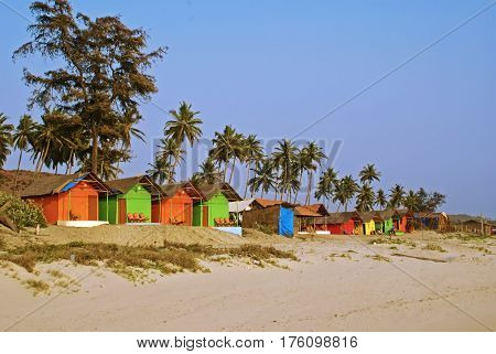 A Row of Colorful Bungalows on a Palm Beach in Goa, South India.