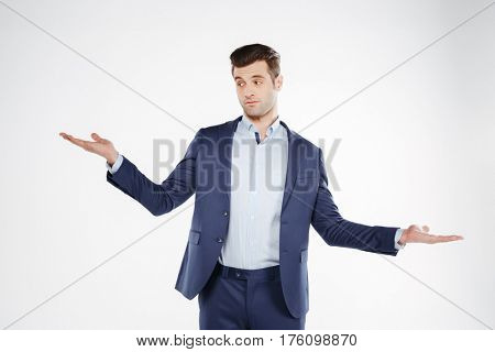 Incomprehensible business man which posing in studio and looking at camera. Isolated white background
