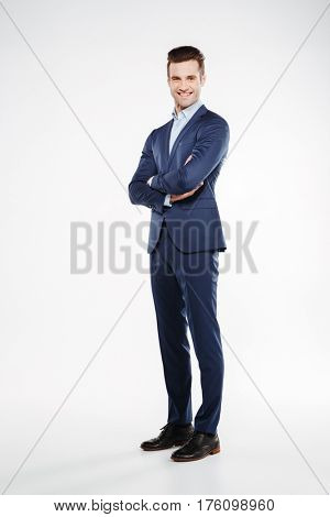 Full length image of smiling business man which posing in studio with crossed arms and looking at camera. Isolated white background