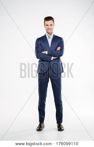 Full length image of smiling man in suit which posing in studio with crossed arms and looking at camera. Isolated white background
