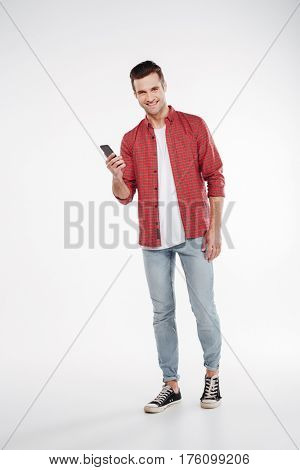 Vertical image of Smiling man in shirt and jeans which holding smartphone and looking at camera. Full length portrait over white background