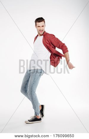 Full length portrait of happy man in shirt and jeans which posing in studio and looking at camera. Full length portrait over white background