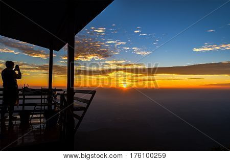 Silhouette of a man standing take a photo on the mountain in on sunrise