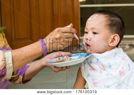 Grand Mother Feeding Food To Thai Baby Boy