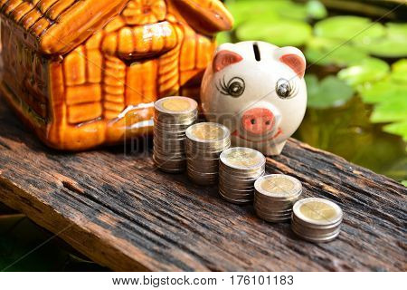 Stack coins beside piggy bank and front of mini house for financial and tax season.
