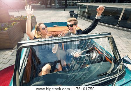 Young and attractive couple sitting in a luxurious retro cabriolet car