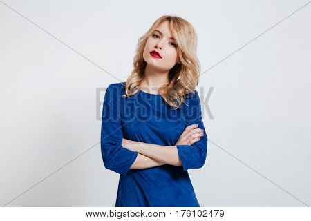 Photo of serious young lady with arms crossed dressed in blue dress standing and posing over white background.