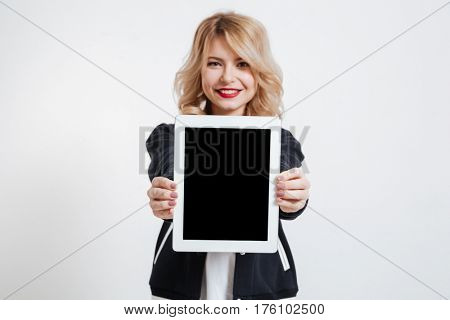 Photo of cheerful young lady standing over white background showing display of tablet computer to camera. Focus on display.