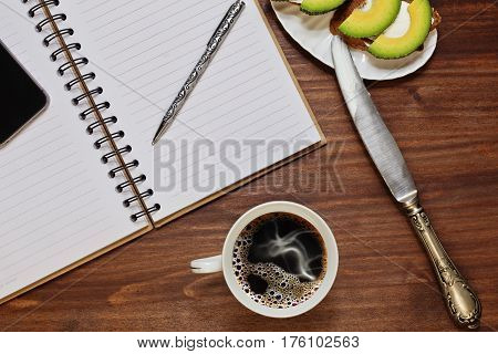 Planning the day with notebook and cell phone while having a breakfast of coffee and simple sandwiches with cheese and avocado slices