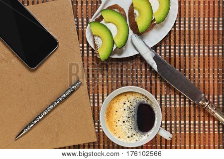 Simple sandwiches with spreading cheese and avocado slices cup with coffee and some planning accessories