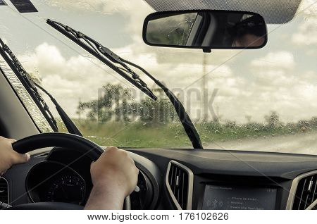 CAMPO GRANDE BRAZIL - FEBRUARY 25 2017: Interior of a moving car on the road on a rainy day with wet windscreen and wiper cleaning the glass. Two hands on the wheel.