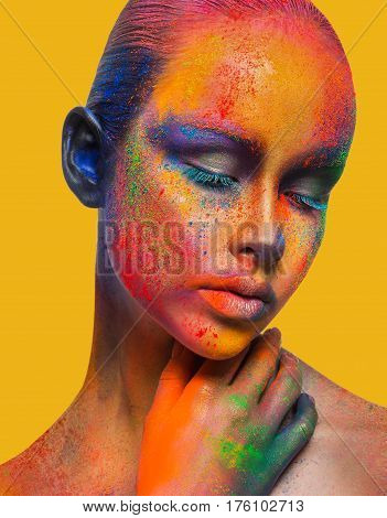 Color fantasy. Holi festival of colors background. Female face art with creative make up. Closeup studio portrait of young fashion model isolated on sandy yellow background