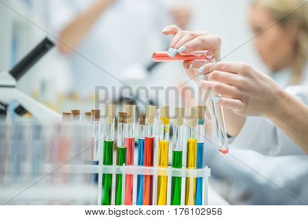 Close-up partial view of female scientist holding test tubes in chemical laboratory