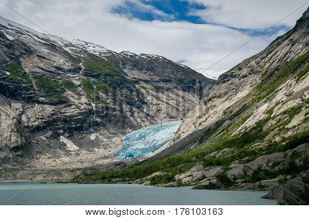 Lake, rocks and glacier - view from popular touristic hiking path to Nigardsbreen Glacier, Norway
