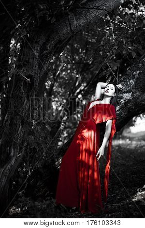 Sexy fashion model resting in fantastical forest. Photo of seductive woman in luxury long red dress laying on tree. Multi-racial Asian Caucasian girl. Fashionable toning. Creative computer colors.