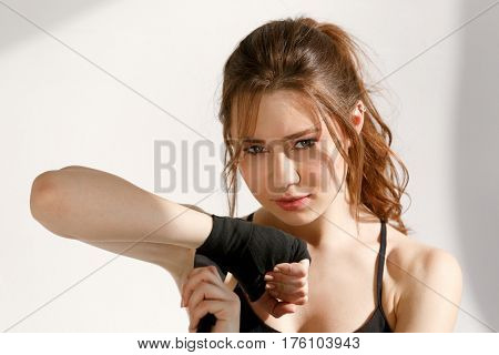 Close up portrait of a fitness woman wraping her hand with boxing bandage isolated on a white background