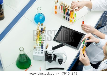 Partial view of young female scientists working with test tubes in chemical laboratory