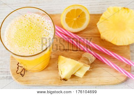 Pineapple,lemon and ginger juice in glassware on wooden table