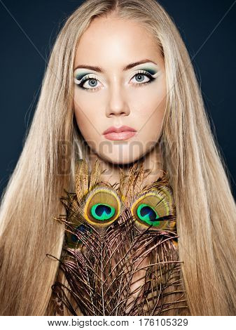 Portrait of gorgeous woman model with evening creative makeup and shiny straight long hair decorated peacock feather.