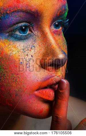 Fashion shooting - crop portrait of beauty model with colorful powder make up show hush sign on dark studio background. Beautiful woman with creative splash makeup. Abstract colourful art make-up