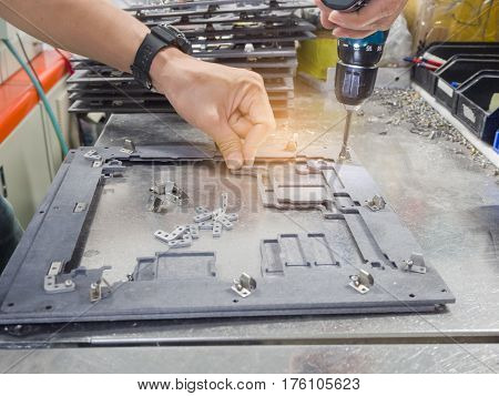 The man working assembly fixture on the table.