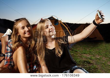 Beautiful blonde girls smiling, making selfie. Camping grill marshmallow. Copy space.