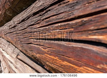 Wall of old obsolete cracked logs. Perspective side view.