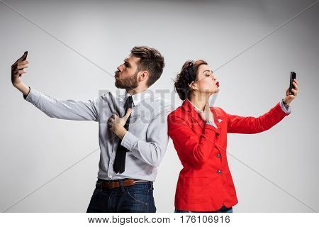 Business concept. The two young colleagues holding mobile phones on gray background and kissing his companion