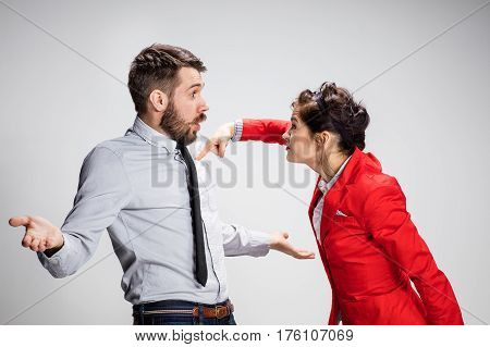 The funny angry business man and woman conflicting on a gray background. Business concept of relationship of colleagues