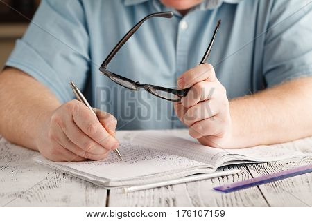 Close Up Male's Hand Writing On Paper, Writing Messy Math,student Hold Glasses , Education Concept