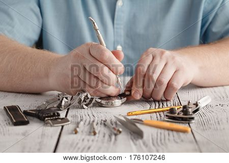 man repaire clock handmade by changing watchband
