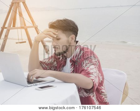 Men working with laptop strictly at the beach.