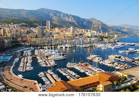 Panoramic view of port of Hercules with luxury yachts and ref roofs of buildings in La Condamine district in Monaco