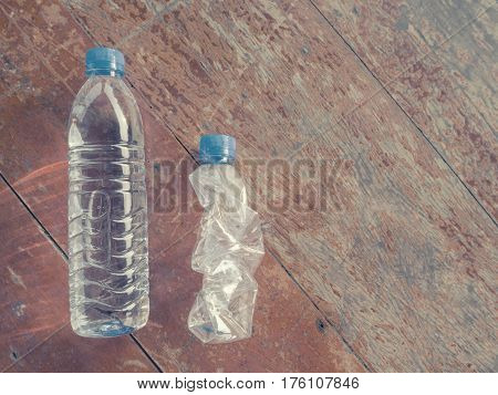 Plastic water bottles with water and no water on dry wood.