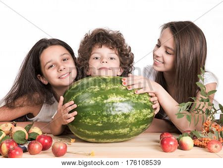 Little brother and two sisters enjoyed enormous variety watermelon. White background. Close-up.