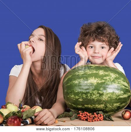 Brother and sister sitting at a table. Wait a delicious watermelon. Sister eating apple. Brother smiling and looking at the camera. Blue background. Close-up.